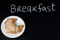 在一块板材的新鲜的新月形面包在黑板,词早餐 免版税库存图片
