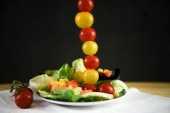 在一块板材的新鲜的明亮的夏天沙拉用在一条高垂直线的微型蕃茄 库存照片
