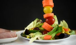 在一块板材的新鲜的火腿沙拉用在一条高垂直线的蕃茄与空间 免版税库存图片