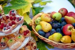 在一块板材的新鲜水果和蛋糕静物画在篮子的有秋叶的 库存图片