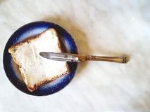在一块板材的方形的三明治有一个蓝色边界和刀子的 与灰色离婚的白色背景 图库摄影