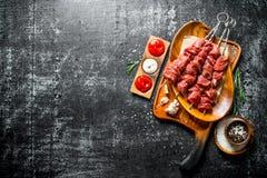 在一块板材的未加工的牛肉kebab用不同的调味汁、大蒜和香料在碗 免版税库存照片