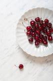在一块板材的樱桃在一张大理石桌上 免版税库存照片