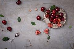 在一块板材的樱桃在灰色土气背景,拷贝空间,顶上的看法 免版税库存图片