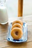 在一块板材的油炸圈饼有一个瓶的在木背景的牛奶由窗口 免版税库存图片
