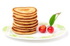 在一块板材的油炸馅饼用樱桃隔绝了白色背景 免版税库存照片