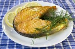 在一块板材的油煎的三文鱼用柠檬和莳萝在一张蓝色方格的桌布 库存照片