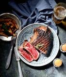 在一块板材的油煎的牛排用迷迭香,烤土豆,刀子,叉子,瓶子用在黑暗的背景的香料 免版税库存图片
