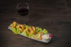 在一块板材的油煎的虾用调味汁和一杯在木背景的酒 库存照片