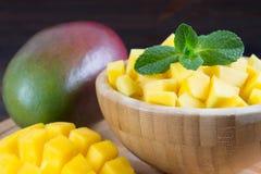 在一块板材的热带水果芒果在木背景,整个或者 免版税库存照片