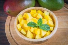 在一块板材的热带水果芒果在木背景,整个或者 库存图片