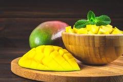 在一块板材的热带水果芒果在木背景,整个或者 免版税库存图片
