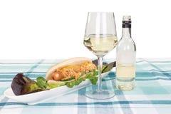 在一块板材的热狗用用玻璃和瓶装饰的沙拉 免版税库存图片