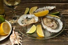 在一块板材的牡蛎有冰和柠檬的,与一杯白色干萄酒在木背景 海鲜,餐馆,精妙的口味 免版税库存照片