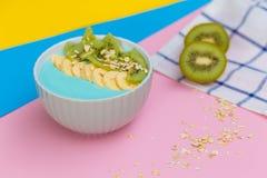 在一块板材的猕猴桃在色的背景 在色的背景的新鲜水果 免版税库存照片