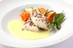 在一块板材的白色鱼用调味汁 图库摄影