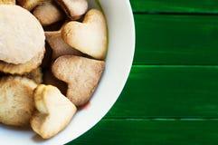 在一块板材的糖屑曲奇饼在绿色木背景 库存照片