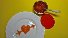 在一块板材的红色鱼子酱以心脏的形式 免版税库存图片