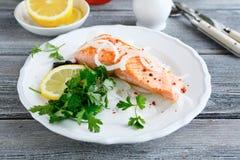 在一块板材的红色鱼用柠檬和荷兰芹 免版税库存图片