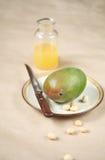 在一块板材的芒果有马卡达姆坚果的 图库摄影