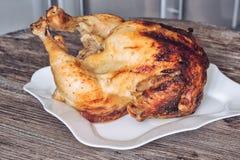 在一块板材的被烘烤的鸡在一张木桌上 与一个金黄外壳的可口鸡 库存照片