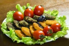 在一块板材的鲜美肉或鱼nagets在绿色莴苣叶子装饰用蕃茄 特写镜头 免版税库存图片