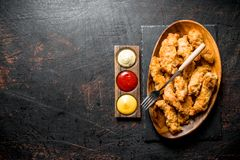 在一块板材的鸡小条有叉子和不同的调味汁的 免版税库存图片