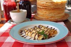 在一块板材的滚动的薄煎饼用蜂蜜 免版税图库摄影