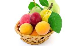 在一块柳条木板材的整个成熟果子在白色背景 免版税库存图片