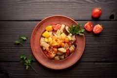 在一块棕色板材和一张木桌的辣菜炖煮的食物 混杂的菜炖煮的食物 库存照片