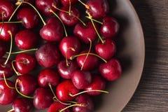 在一块棕色板材的红色樱桃在一张木桌上 夏天食物,健康吃 有机,素食,素食主义者,饮食,糖尿病 库存图片