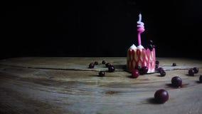 在一块欢乐桃红色杯形蛋糕的一个灼烧的蜡烛在葡萄酒木桌上吹灭 手拾起一个蜡烛 紧密,在黑色 股票录像