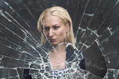 在一块残破的玻璃后的妇女 库存图片