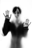 在一块毛玻璃后的朦胧的妇女形象 免版税库存照片