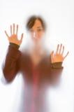 在一块毛玻璃后的朦胧的妇女形象 免版税图库摄影