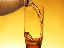 在一块清楚的玻璃用冷的苏打水填装了在塑料外面 库存图片