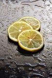 在一块湿玻璃的柠檬。 免版税库存图片