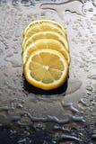 在一块湿玻璃的柠檬。 免版税图库摄影