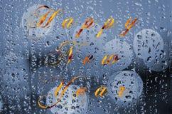 在一块湿玻璃写的新年好消息 夜城市生活通过挡风玻璃:黑暗和雨 图库摄影