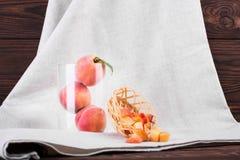 在一块灰色布料的明亮的水多的桃子 三个整个桃子特写镜头在一个玻璃花瓶和一个条板箱的用被切的果子 库存图片