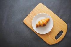 在一块点心白色板材的一个可口新月形面包在黑暗的工艺纸 免版税库存图片