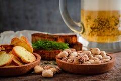 在一块玻璃、开心果、黑麦油煎方型小面包片和薄脆饼干的啤酒在木头 库存照片
