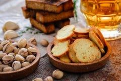 在一块玻璃、开心果、黑麦油煎方型小面包片和薄脆饼干的啤酒在木头 免版税库存图片