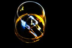 在一块玻璃与冰块,金黄颜色威士忌酒的苏格兰威士忌酒 免版税库存照片
