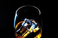 在一块玻璃与冰块,金黄颜色威士忌酒的苏格兰威士忌酒 免版税库存图片