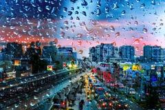 在一块玻璃后的夜城市与雨珠 免版税库存图片