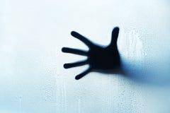 在一块玻璃后的蓝色手剪影用水滴下 免版税库存照片
