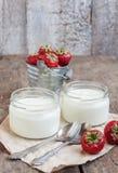 在一块玻璃和一个桶的酸奶用在向求爱的新鲜的草莓 免版税库存图片