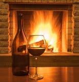 在一块玻璃和瓶的红葡萄酒,在舒适壁炉前 库存图片