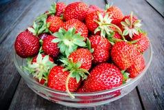 在一块玻璃板的水多的草莓在木背景 免版税库存照片